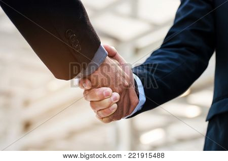 close up of business man in suit handshake after finishing up a business meeting in the city, congratulation, success, meeting, partner, teamwork, community and connection concept, selective focus