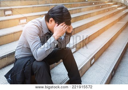 disappointed, sadness or stressed medium aged unemployed asian business man sitting on the walkway in the city after fired from job, business problem, unemployment, financial and investment concept