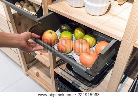 Hand pulling metal kitchen drawer filled with fake apples for display. Detail of furniture for home organizer.
