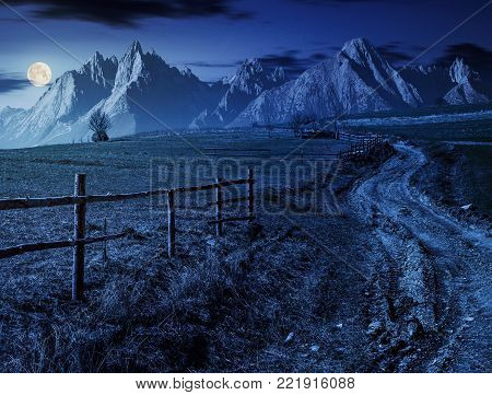 road through rural fields in mountainous area. composite imagery of agricultural countryside in springtime at night in full moon light. wooden fence along the grassy fields on hillside