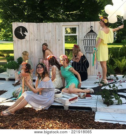 Tallinn, Estonia - June 25, 2016: Stylish female friends with flower wreaths are enjoying hen-party or bridal shower party in the park.