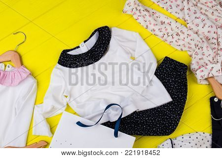 Children's clothes on yellow table. Mess in girl's room. Pajamas and loungewear.
