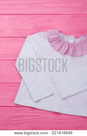 White blouse with pink collar. Lightweight soft cotton and ruffles. New collection of kids' clothing.