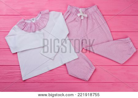 Girls' top and pants pajama set on wooden background. Pink and white. Comfy garments for good sleep.