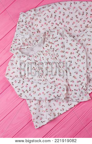 Girls' sleepwear on pink table. White fabric with fine flower pattern. Simple design with cute ruffles.