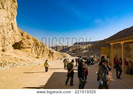 Valley of the Kings, Egypt. February 18, 2017: Tourists resting at the bottom of the valley surrounded by very arid mountains on a sunny and hot day.