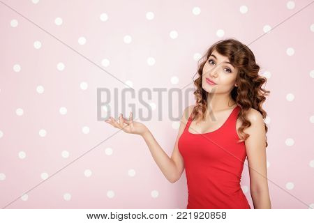 beautiful young curly woman showing copy spase on pink background.
