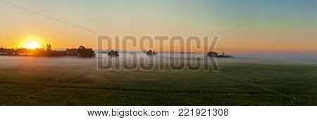 Dawn in a meadow in the mist against a background of clear sky. Dawn in the meadow in the fog.