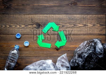 Green paper recycling sign among waste materials plastic and polyethylene on dark wooden background top view.