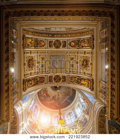 ST PETERSBURG, RUSSIA - AUGUST 15, 2017. Ceiling ornated with sculptures and Bible paintings in the interior of the St Isaac Cathedral in St Petersburg, Russia. Panoramic view of St Petersburg Russia landmark