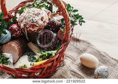 Stylish Easter Basket With Food. Horseradish, Beetroot, Ham, Butter, Buxus, Sausage And Painted Eggs