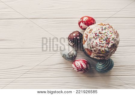 happy easter flat lay, stylish easter bread and painted eggs on rustic wooden background top view.  greeting card. space for text