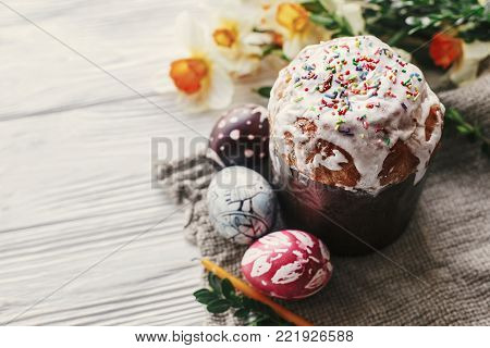 stylish easter bread and painted eggs on rustic wooden background with candle yellow flowers and greenery. happy easter, greeting card. space for text