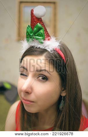 A suspicious and doubtful girl in a Christmas hat winks at the camera.