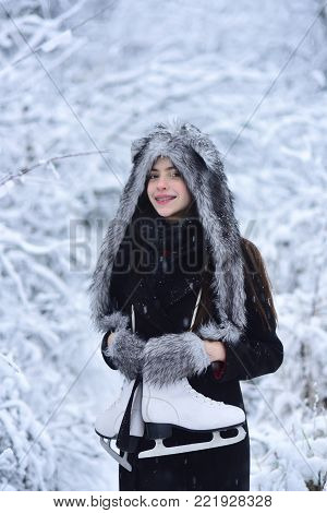 Girl smile with pair of figure skates at trees in snow. Woman with skating shoes in winter clothes in snowy forest. Sport, activity, health. Ice skating concept. Vacation, holidays, hobby, lifestyle.