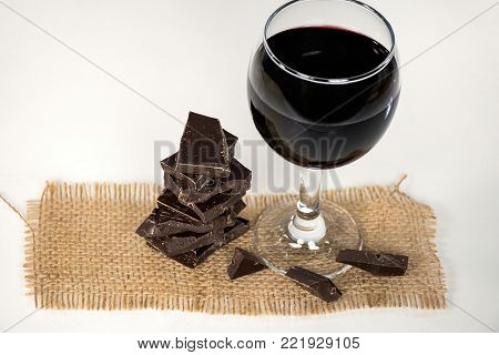 red wine in stemware with dark chocolate candy on brown burlap