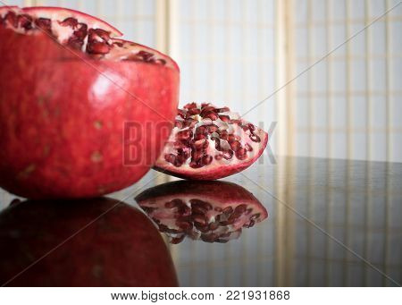 One pomegranate with the top part cut off and set beside on the reflective counter.