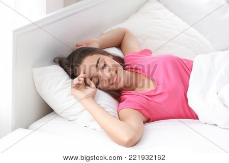 Young beautiful woman awaking in light room