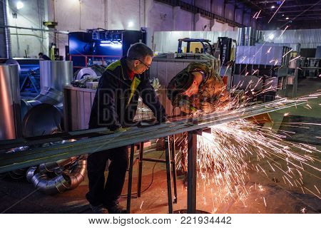 Voronezh, Russia Circa 2017:Metal workers cutting metal parts using electric circular grinder in metalwork factory. Sparks while grinding.