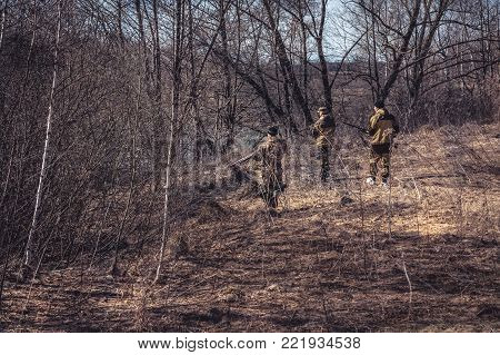 Hunting scene with group of hunters in camouflage stealing in dry forest during hunting season