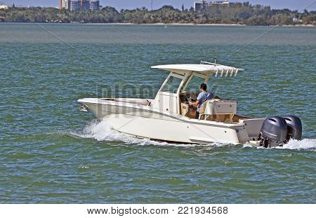 Sport fishing boat powered by two outboard engines cruising the florida intra-coastal waterway off Miami Beach