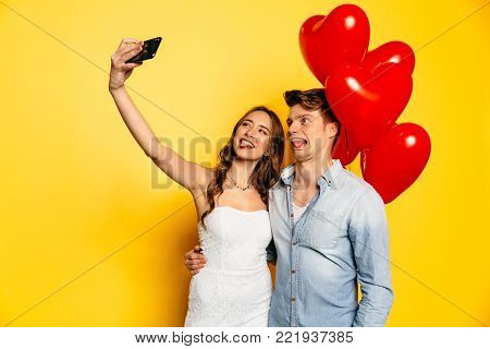 Crazy Couple Showing Tongues While Taking Selfie With Balloons