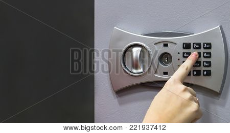 girl using forefinger / index finger pushing number button on grey safe to unlock safe or set password for safe, concept. Free space