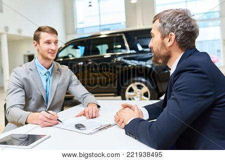 Portrait of successful young man buying brand new luxury car in showroom, signing purchase contract while sitting across table from mature salesman