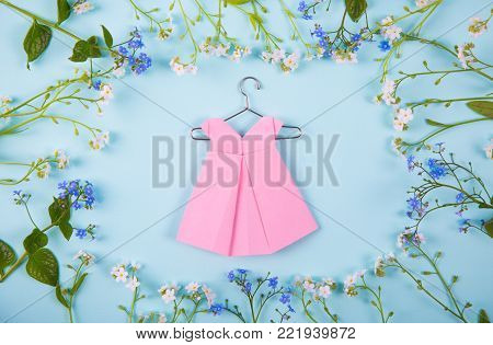 Paper Origami Dress On Hanger Surrounded With Blue And White Little Flowers On Light Mint Background