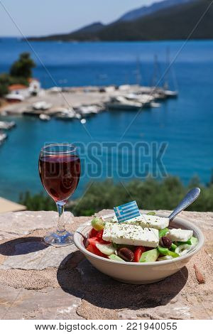 A glass of red wine and bowl of greek salad with greek flag on a stone terrace by the sea view, summer greek holidays concept. Vertical. Daylight.