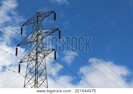 High voltage electricity pylon or power transmission tower. Blue sky with white clouds in the background and a tree in the foreground. poster