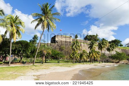 The Fort Saint Louis and caribbean beach in the foreground , Martinique island , French West Indies.