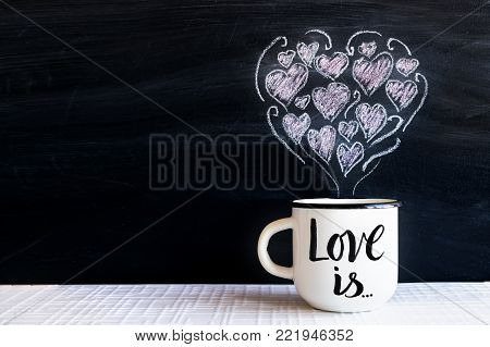 White cup with hand lettering text LOVE IS and chalk-drawn small hearts in the form of a heart on the blackboard. Valentine's Day, Love and romance concept. Valentine's Day blackboard. Copy space