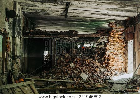Interior of destructed building by earthquake or war, pile of bricks and rubbish, toned