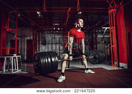 Muscular fitness man doing deadlift a barbell in modern fitness center. Functional training. Snatch exercise