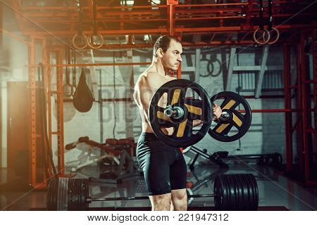 Athlete training biceps in a gym. Functional training workout