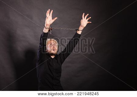 No freedom, social problems concept. Furious man with chained hands, studio shot on dark grunge background