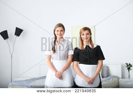 Young chambermaids in uniform indoors