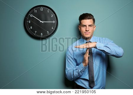 Handsome manager showing time out gesture near color wall with clock