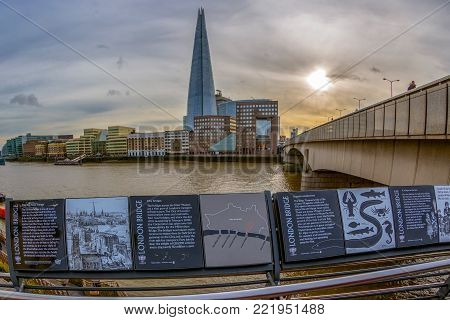 LONDON, ENGLAND - NOVEMBER 27, 2017: Overlooking the Shard Tower and the banks of Thames river below London Bridge. Inscriptions with historical description for tourists. Sunset time.