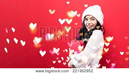 Happy young woman holding a big heart gift box with heart lighs