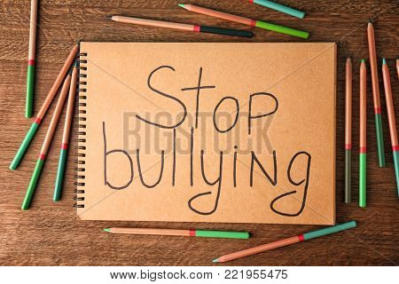 "Notebook with text ""Stop bullying"" on wooden background poster"