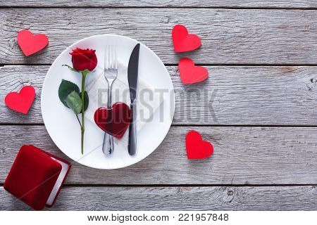 Engagement proposal background. Top view of rose, cutlery and glossy glass heart on plate, paper hearts and present box. Copy space on rustic wood. Valentine's Day, love, romantic concept