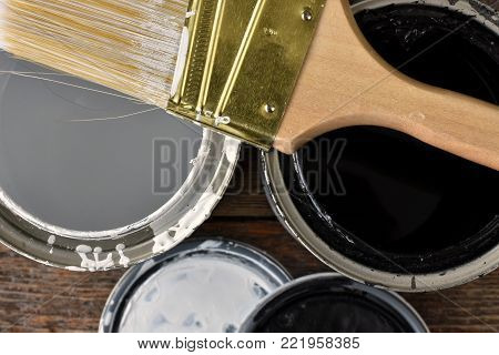 A top view image of old paint cans with white paint and black paint.