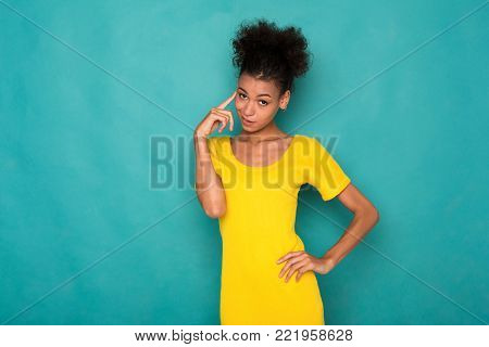 Pensive african-american woman standing on blue background and thinking. Young girl posing and making decision, touching her head, brainstorming concept
