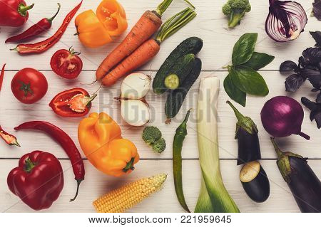 Rainbow collection of fresh organic vegetables. Vibrant harvest background with cooking ingredients. Top view on peppers, carrots, leek, egplants, onions, herbs and spices. Healthy eating concept