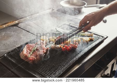 Unrecognizable male chef cooking medium beef steak and vegetables on grill. Healthy exclusive food prepared at professional kithen, closeup