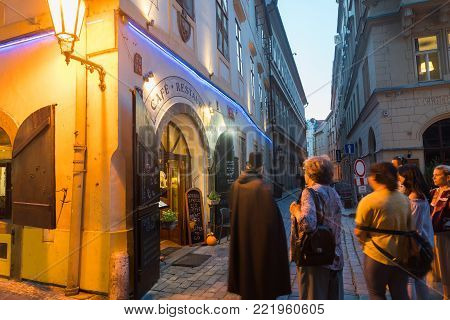 PRAGUE, CZECH REPUBLIC,- 29 AUGUST 29, 2017; Street corner under glow of lamp and entrance to restaurant with narrow lane people on walking tour blurred by long exposure.