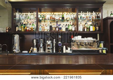 Bar counter with alcohol bottles assortment. Barroom in restaurant, hotel, pub copy space. Cafe background