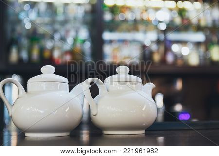 Bar counter with two white teapots, blurred alcohol bottles assortment on background. Barroom in restaurant, hotel, pub, cafe, copy space.
